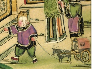 A child playing with a toy ox-wagon. He wears a tiger hat.
