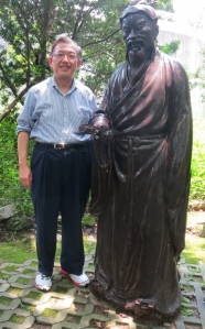 Patrick standing behind the statue of Shu Sheng